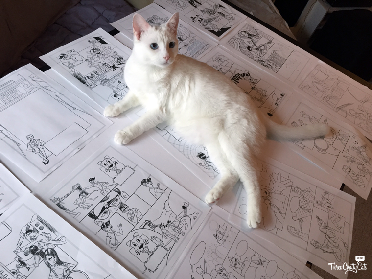 white cat lying on comic book drawings