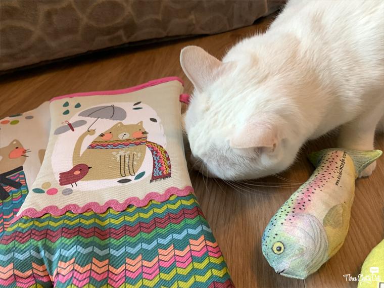 white cat sniffing oven mitt